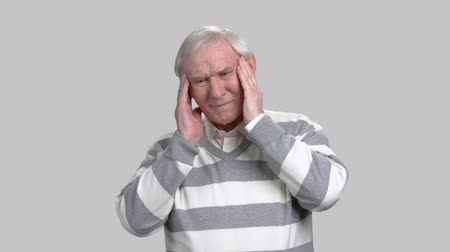 cheerless : Senior man with headache, grey background. Sad cheerless elderly man holding his temples and massaging them while suffering from headache. Strong migraine concept.