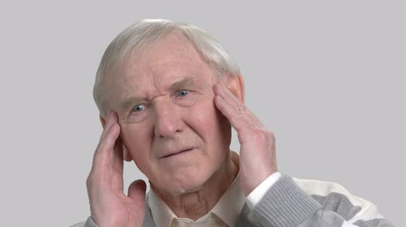 cheerless : Caucasian pensioner feeling pain in his temples. Old european man suffering from terrible headache, grey background. Pain and facial expression.