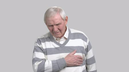 chest pain : Mature man with painful feelings in chest. Elderly man suffering from heart-attack, grey background. How to recognize heart-attack.