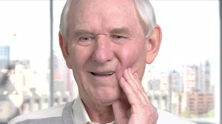 зубная боль : Senior man feeling bad because of toothache. Cheerless elderly man suffering from problem with teeth, window city background.