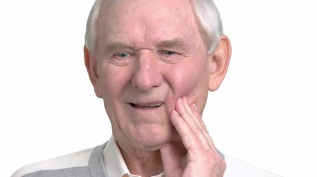 зубная боль : Close up old man having strong toothache. Senior man with sensitive toothache crown problem, white background. Dental care concept.
