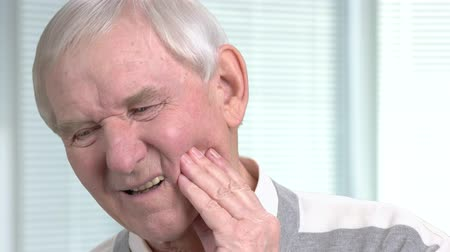 口腔病学 : Unhappy senior man having toothache. Stressed elderly man with terrible toothache on blurred background close up.