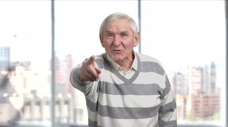 descontente : Displeased senior man gesturing with finger. Annoyed elderly man arguing with someone, window city background.