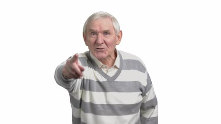 descontente : Displeased emotional pensioner, white background. Mad elderly man arguing and pointing with index finger, isolated on white background. Dissatisfaction and conflict concept. Vídeos