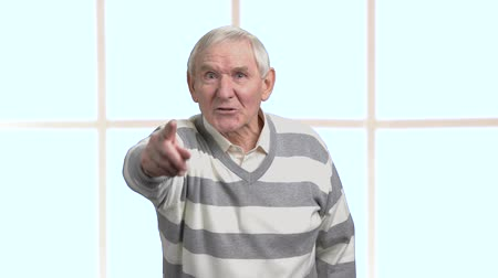 descontente : Angry senior man, blurred background. Mad frustrated pensioner arguing with someone and gesturing with finger. Social protest of pensioner.