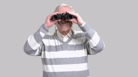binocular : Elderly man with binoculars, grey background. Aged man in casual sweater looking through binoculars. Retired man with binoculars. Stock Footage