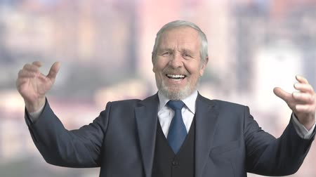 emelt : Joyful elderly businessman, slow motion. Excited senior man in business suit clenched his fists on blurred background. Gesture of victory and success.