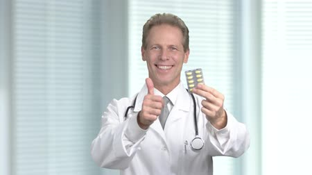 gesture pack : Doctor with pills gesturing thumb up. Male cheerful physician showing blister pack pills, blurred background. Mature successful medical specialist. Pharmaceutical and medicine concept.