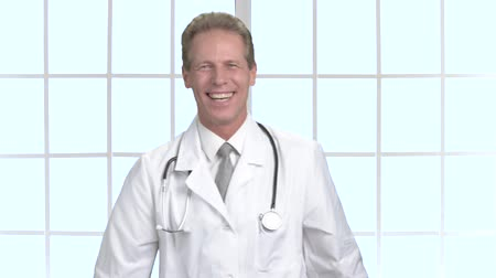 żart : Joyful male doctor laughing and gesturing. Happy middle-aged doctor on window background. Human facial expressions.