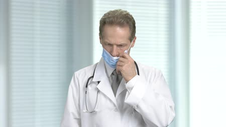 sebész : Sad doctor takes off the protective mask. Unhappy tired male doctor on blurred background. Stock mozgókép
