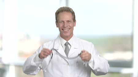 cardiologista : Happy male cardiologist on blurred background. Cheerful male doctor with stethoscope gesturing thumb up on blurred background.
