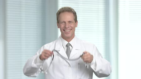 cardiologista : Joyful cardiologist showing thumb up. Positive middle-aged doctor putting on stethoscope and gesturing thumb up, blurred background.
