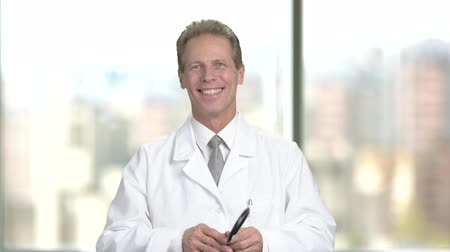 cardiologista : Cheerful male doctor with stethoscope. Happy smiling professional cardiologist showing ok gesture and looking at camera. Stock Footage