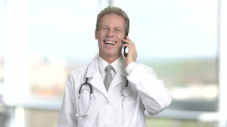 cardiologista : Smiling cardiologist talking on phone. Happy male doctor talking on phone and gesturing with hand, blurred background. Gesture of success.