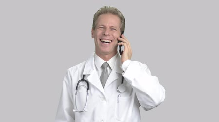 консультация : Excited male doctor talking on phone. Cheerful cardiologist talking on mobile phone and gesturing in excitement, grey background. Concept of winner.