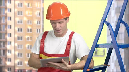 drabina : Smiling manual worker with pc tablet. Portrait of happy worker in uniform holding digital tablet, buildings background. Construction, building, people and maintenance concept.