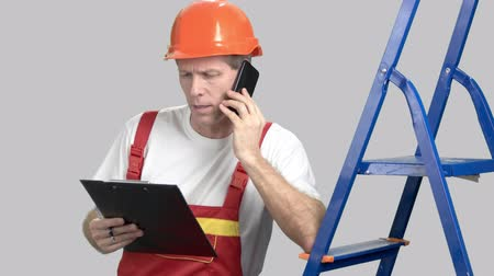 ciddi : Serious construction worker with mobile phone. Angry mature foreman looking at clipboard and talking on mobile phone, grey background. Stok Video