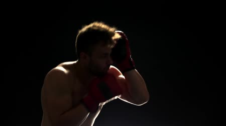 férfias : Young handsome sportsman in gloves is boxing. Young muscular fighter training on black background, slow motion. Young masculine caucasian male athlete.