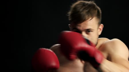 точность : Young sportive man training box close up. Young handsome boxer practicing some kicks on black background. Persistence, training, competition.