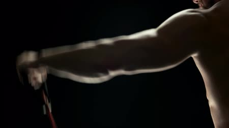 gumka : Bodybuilder doing resistance band exercises. Young man bodybuilder working out with rubber band close up. Sexy muscular shoulders of young sportsman. Wideo