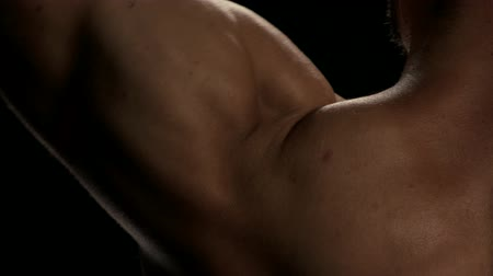 maior : Close up man lifting heavy dumbbell. Detail of mans biceps flexing on black background. Tips for bigger and strong arms.