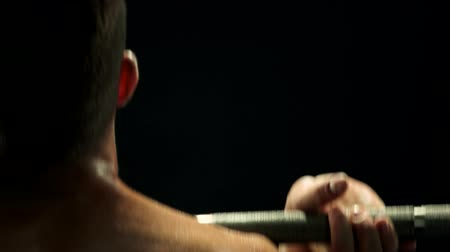 dope : Close up sweaty muscular man training with barbell. Rear view shirtless athletic man working with heavy equipment, dark background. Stock Footage