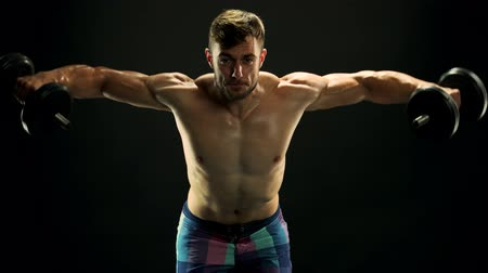 sports nutrition : Muscular fitness man training with dumbbells. Handsome athlete having workout with dumbbells on black background. Sweaty body and hard efforts. Stock Footage