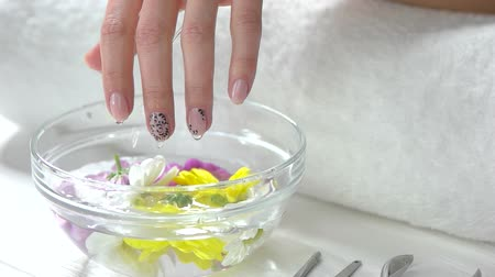 unha : Glass bowl and hands, slow motion. Wet female hands, aroma bath with water and flowers, white towel on table. Woman hands receiving spa therapy.