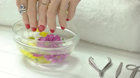 chrysanthemum : Woman taking out hands from aroma bath. Slow motion senior woman taking out her hands from glass bowl with water and chrysanthemums. Spa for hands.
