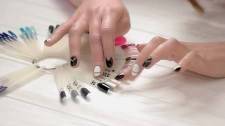 lakier do paznokci : Hands choosing nail color, slow motion. Young woman hands with stylish manicure and nail color samples on table in beauty salon.