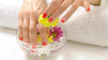 chryzantema : Hands aroma therapy, slow motion. Beautiful female hands receiving spa procedure with water and flowers in nail salon. Skin care and treatment.