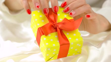 womanhood : Beautiful hands holding gift box. Slow motion delicate female hands with red manicure holding box with present on white silk background close up. Holidays and celebrations concept.