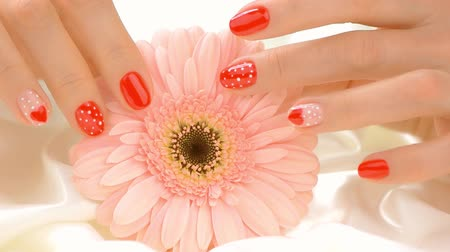 duygusallık : Flower and manicured hands touches, slow motion. Well-groomed hands of young woman caress peach gerbera flower on white silk close up. Tidiness and delicacy concept.