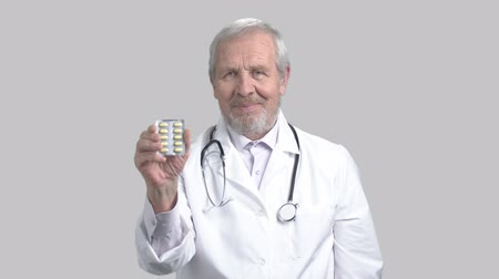 gesture pack : Cheerful caucasian doctor offering pills. Senior caucasian male doctor showing new effective medical pills. Elderly doctor gesturing thumb up on grey background. Stock Footage