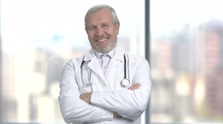 hanedan arması : Senior handsome doctor with arms crossed. Happy older doctor smiling and looking at camera with folded arms, blurred background.