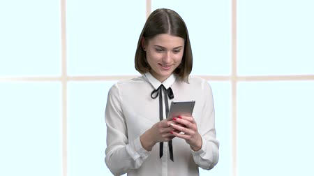rövidszőrű : Beautiful woman using her smartphone at office. Attractive young woman in white blouse texting a message on her phone, abstract window background. Stock mozgókép