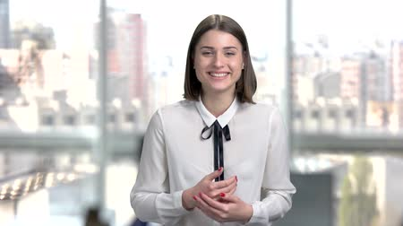şaka : Portrait of young cheerful business woman. Modern brunette lady is smiling on window city background. Happy office manager. Stok Video