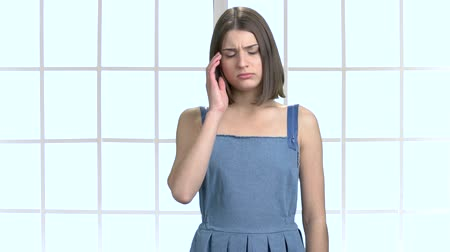 dungarees : Young caucasian lady having headache. Sad young female suffering from stress and pain in temple on abstract window background. Problems, fatigue, stress and headache. Stock Footage