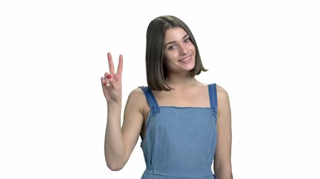 dungarees : Portrait of young smiling woman, white background. Happy cheerful girl showing victory sign isolated on white background. Give peace a chance.