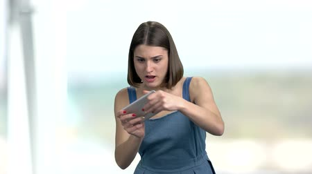 mobile game : Funny young woman playing on smartphone. Happy cheerful girl using touch screen phone on blurred background. Stock Footage