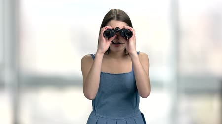 dungarees : Young curious woman with binoculars. Pretty girl with bioculars on blurred background. Beautiful female explorer.