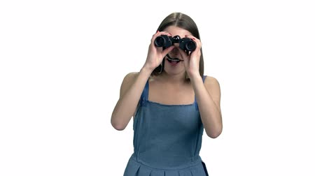 denim : Young woman looking through binoculars. Portrait of beautiful excited lady with binoculars isolated on white background. Facial expression of excitement.