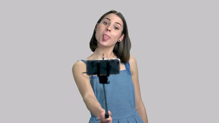 карикатура : Young woman taking selfie with monopod. Portrait of young well-dressed girl making funny face while holding selfie stick, gray background.