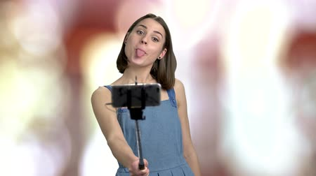 dungarees : Young woman making grimace. Brunette young girl smiling and showing peace gesture while holding monopod on blurred background.