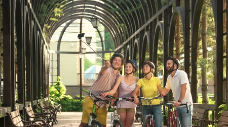 alma : Four beautiful friends with monopod outdoors. Young cheerful male and female cyclists taking a photo with selfie stick.