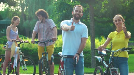 прокат : Couple of young cyclists showing thumbs up. Happy cheerful young man and woman with bicycles outdoors. Happy vacation together. Стоковые видеозаписи