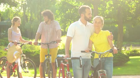 прокат : Couple of young cyclists kissing outdoors. Happy young man and woman with bicycles outdoors. Beautiful sunny day.