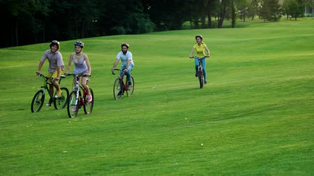ゴルフ : Four cheerful students cycling on green lawn. Group of young bikers cycling through park. Happy summe holiday. 動画素材