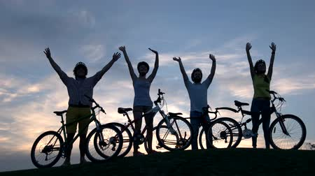 unutulmayan : Company of young cyclists at sunset sky. Group of young people with bicycles waving with hands on sky background. Best rest outdoors.