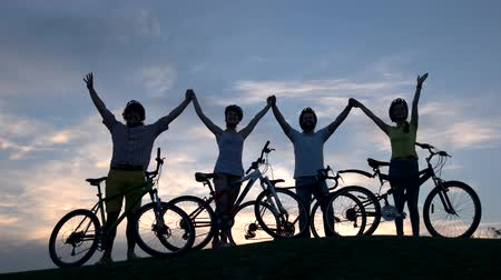 bisiklete binme : Young cyclists holding hands at sunset. Four young persons with bicycles walking cheerfully together along sunset horizon. Rest and healthy lifestyle. Stok Video